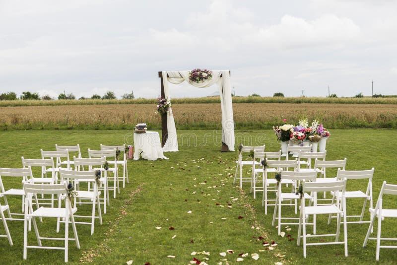 在一个领域的美好的婚礼与白色椅子 婚礼的地方与婚礼曲拱装饰与 库存图片