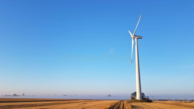 在一个领域的风轮机在晴朗的早晨 免版税库存照片