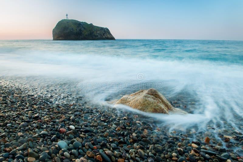 在一个风景有卵石花纹的海滩的清早 库存图片