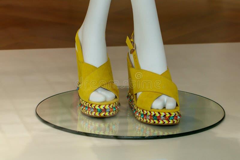 在一个黄色平台凉鞋的窗口里 妇女的鞋子 免版税库存图片