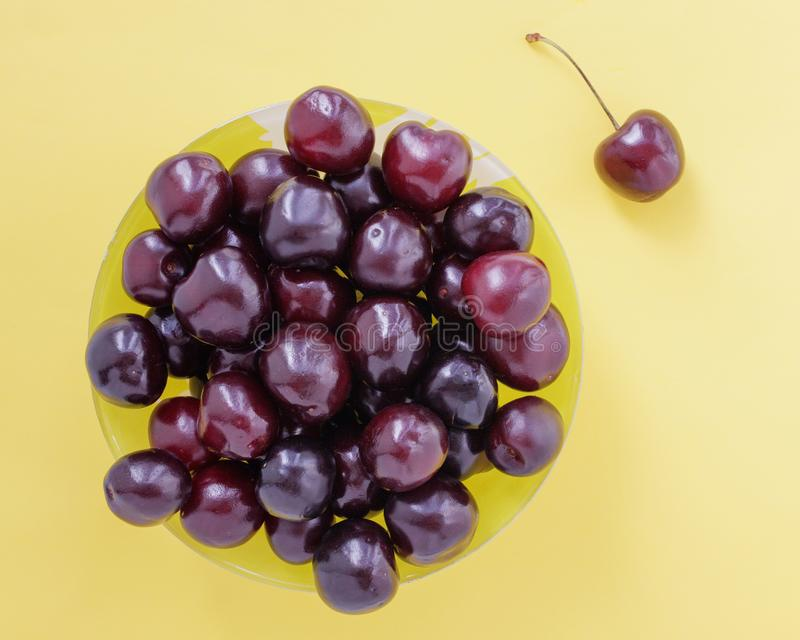 在一个黄色杯子和一个唯一莓果的红色甜樱桃在米黄背景 库存图片