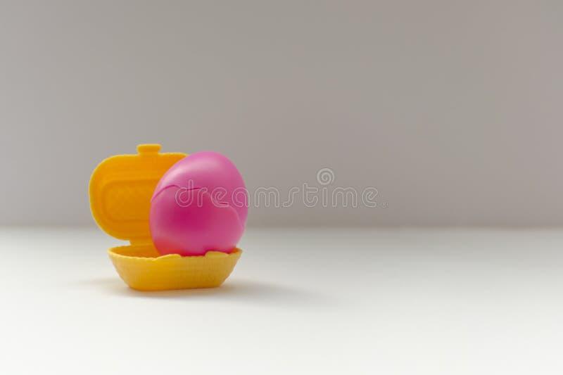 在一个黄色篮子的复活节桃红色鸡蛋 免版税库存照片