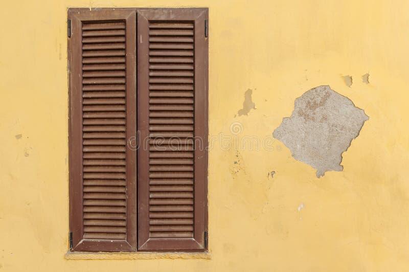 在一个黄色老水泥房子的布朗木纹理窗架 免版税库存图片
