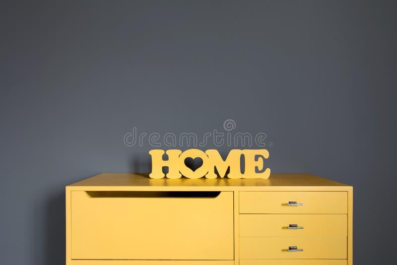 在一个黄色葡萄酒木五斗橱的黄色木题字`房子` 免版税库存照片