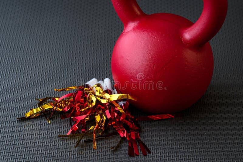 在一个黑健身房地板上的红色kettlebell与红色和金发出大声音的人 库存照片