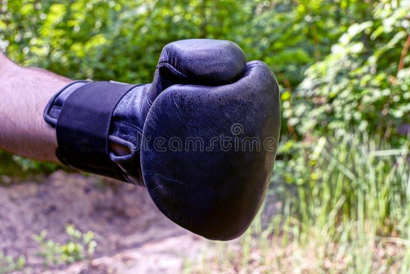 在一个黑拳击手套的一只手在街道上 图库摄影