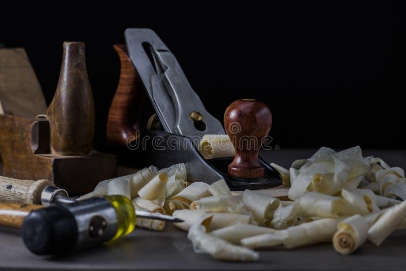 在一个黑暗的喜怒无常的设置的老和新的木材加工工具 库存图片