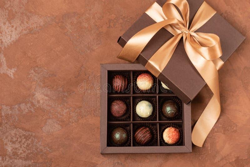 在一个黑暗的纸箱的巧克力糖有在棕色织地不很细背景的一缎带的 平的位置 欢乐概念 免版税库存图片