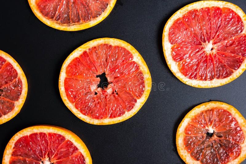 在一个黑暗的背景样式的切的葡萄柚 免版税库存照片