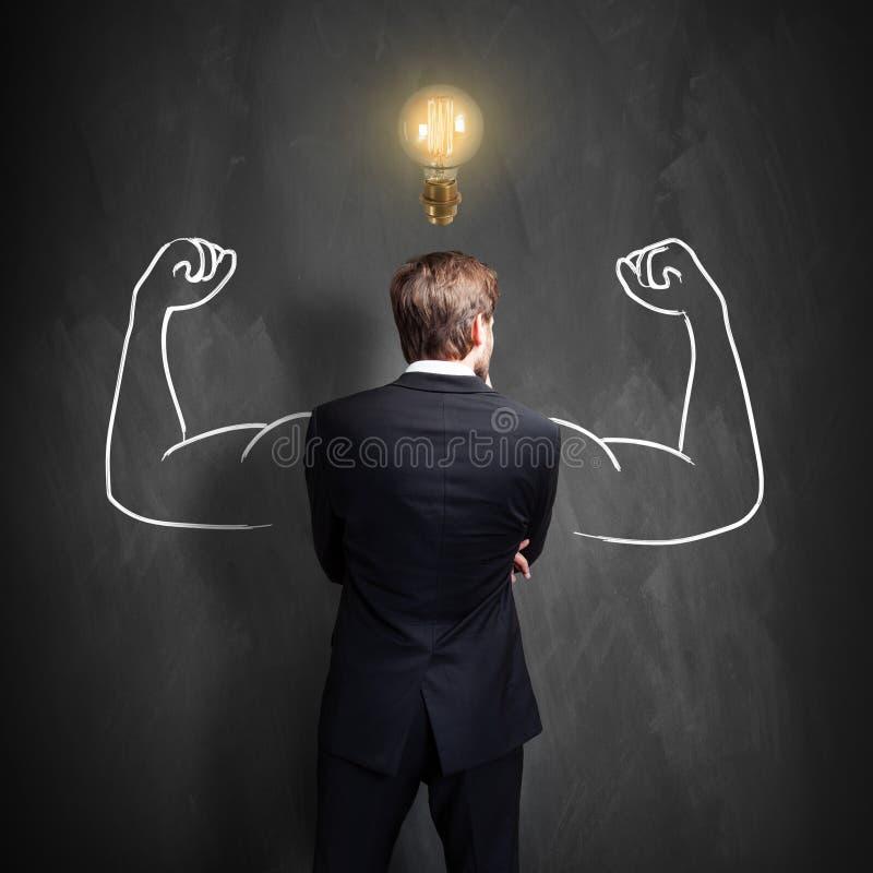 在一个黑板前面的成功的商人身分有在他的头的一个明亮的电灯泡的 免版税库存照片