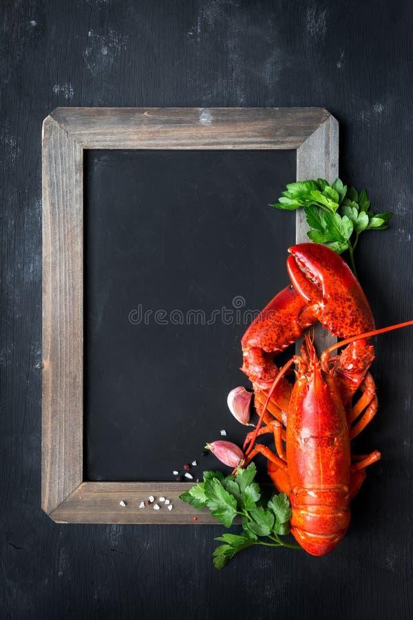 在一个黑板的被蒸的红色龙虾有copyspace的 库存照片