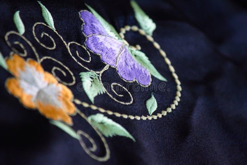 在一个黑枕头的五颜六色的刺绣设计 库存照片