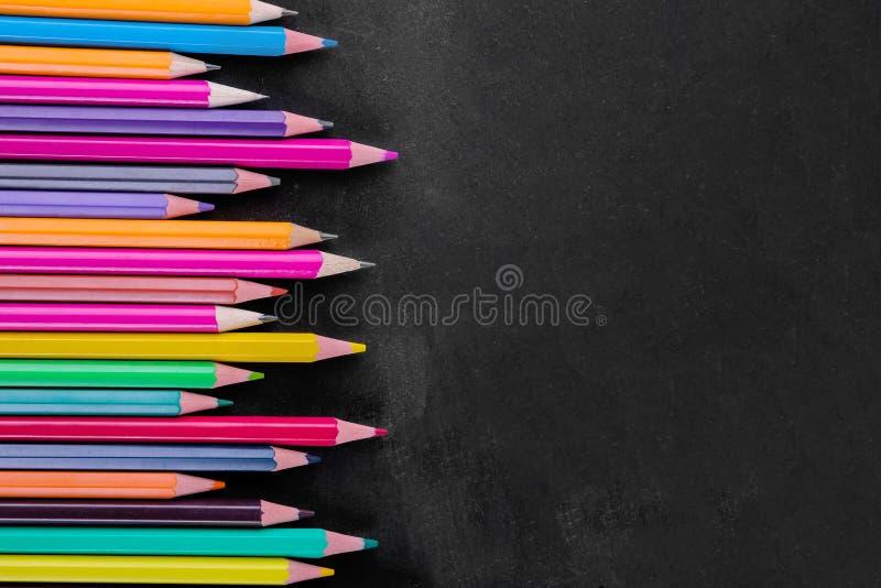 在一个黑校务委员会的多彩多姿的铅笔与题字的一个地方 库存照片