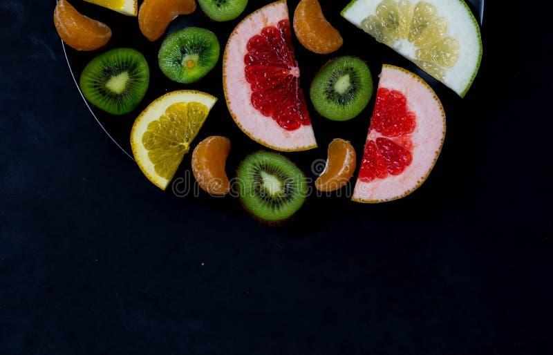 在一个黑碗的切细的明亮的生动的精采黄绿色橙红柑橘葡萄柚橙色普通话糖果猕猴桃在a 库存照片