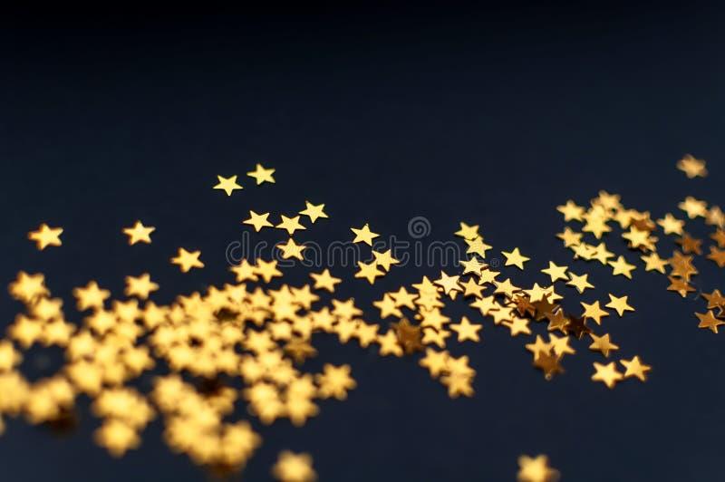 在一个黑背景、顶视图、狂欢节、夜党邀请或者欢乐背景,繁星之夜的微小的金黄星 库存照片
