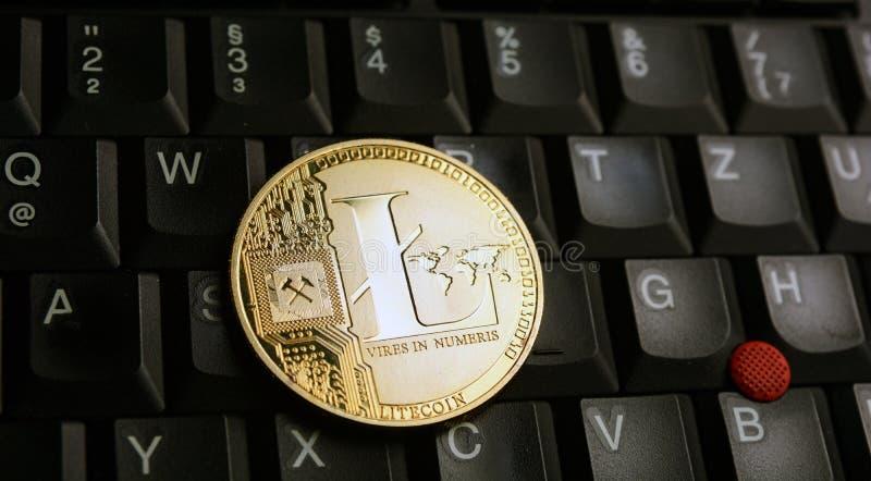 在一个黑膝上型计算机键盘的金黄Litecoin国际航空测量中心硬币 免版税库存照片