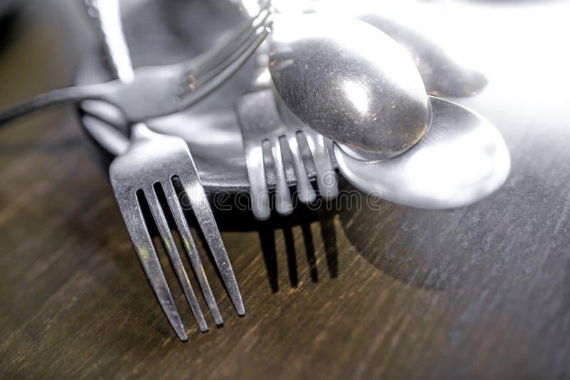 在一个黑色的盘子和叉子安置的匙子在窗口在房子里发光的一张木桌 r 免版税库存图片