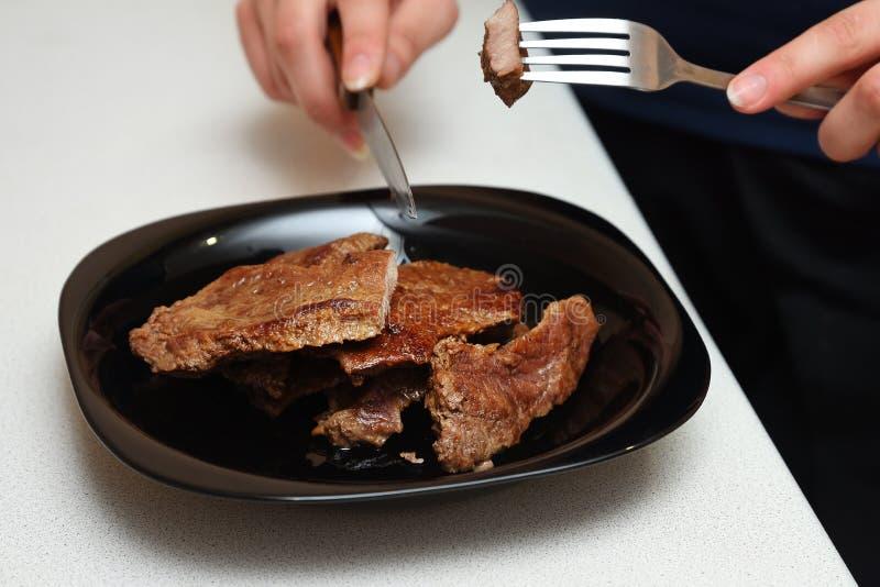 在一个黑色的盘子的油煎的肉采取与叉子和 图库摄影