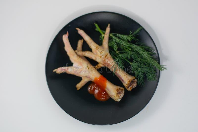 在一个黑色的盘子的烤鸡腿 库存图片