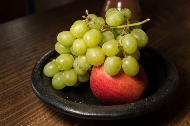 在一个黑色的盘子的红色苹果和绿色葡萄 库存照片
