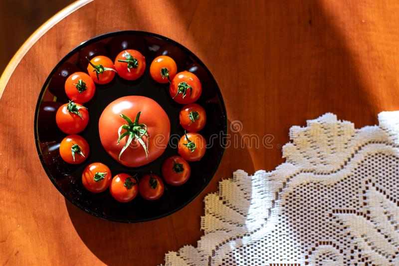 在一个黑色的盘子的红色蕃茄在笔记薄旁边的厨房用桌上 免版税库存照片