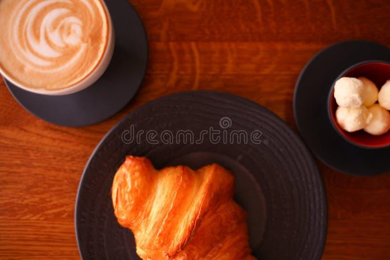 在一个黑色的盘子的被烘烤的新月形面包有加奶咖啡杯子和黄油的 面包店餐馆生活方式 免版税库存图片