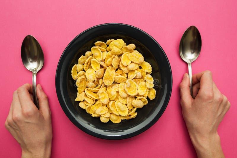 在一个黑色的盘子的黄色玉米片在桃红色背景 有匙子的手 库存照片
