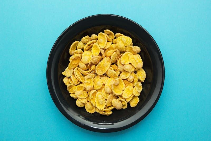 在一个黑色的盘子的黄色玉米片在蓝色背景 免版税库存照片