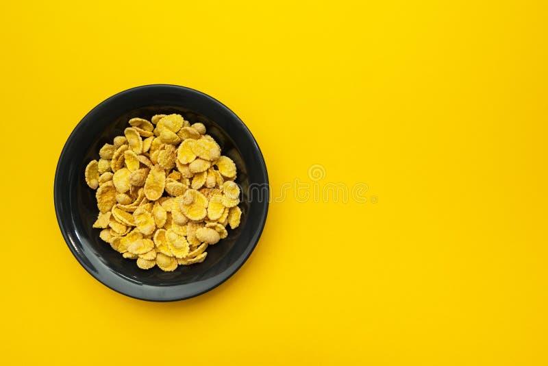 在一个黑色的盘子的黄色玉米片在黄色背景 安置文本 免版税库存照片