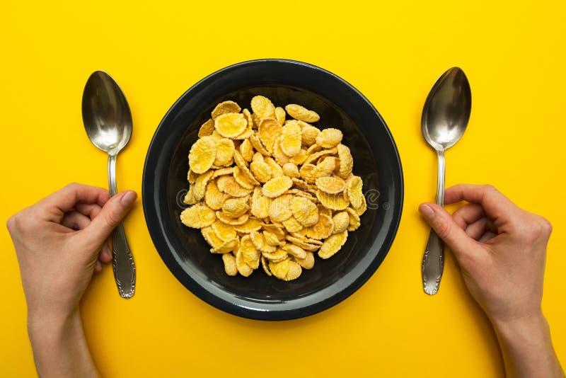 在一个黑色的盘子的黄色玉米片在黄色背景 有匙子的手,吃用两只手 免版税库存照片