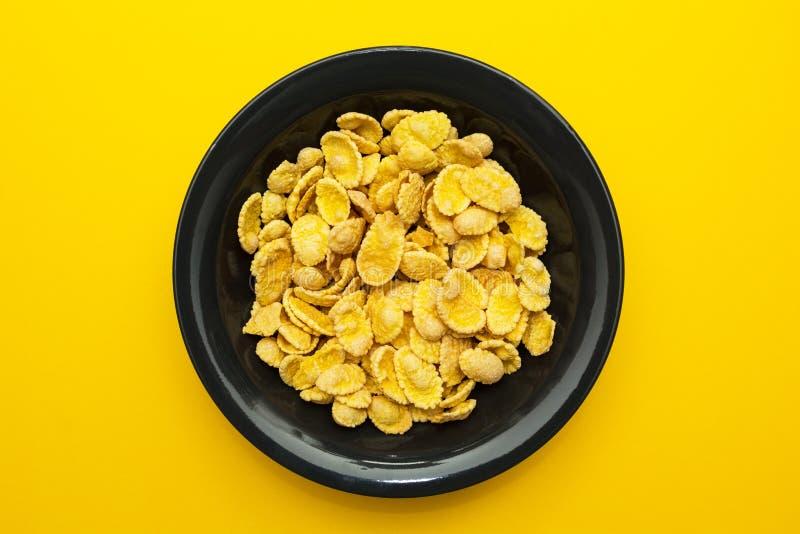 在一个黑色的盘子的黄色玉米片在黄色背景 图库摄影