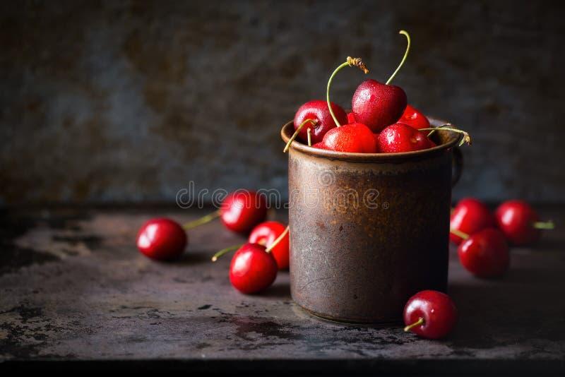 在一个黑褐色杯子的红色成熟樱桃 免版税库存照片