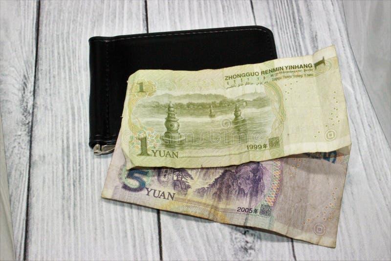 在一个黑钱包的中国1张和5张元钞票在灰色背景 免版税库存图片