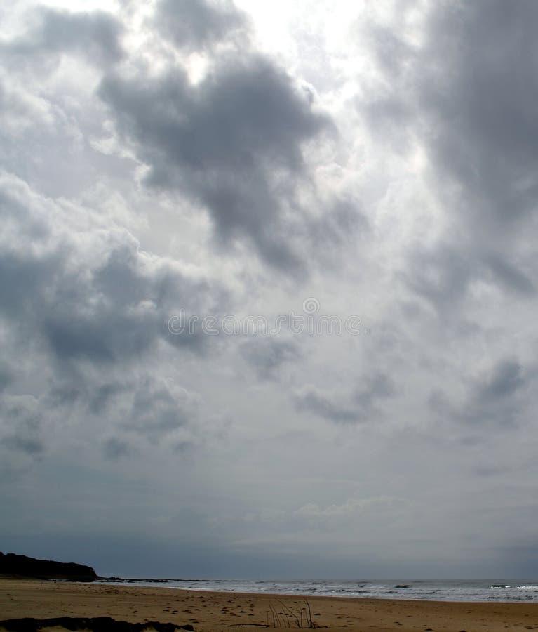 在一个离开的海滩的多云天空 图库摄影
