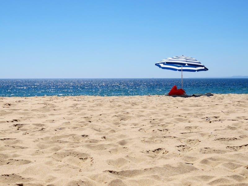 在一个离开的海滩的遮阳伞 免版税库存图片