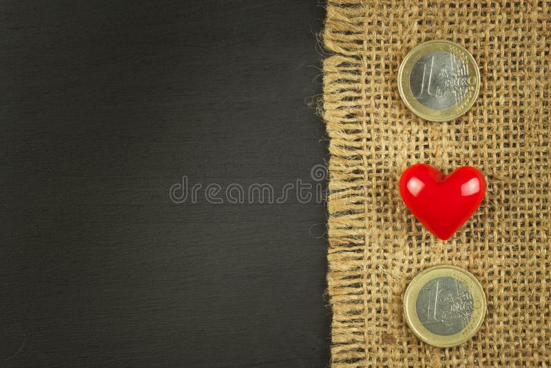 在一个黑木板的老粗麻布有合法的欧洲硬币的 免版税图库摄影