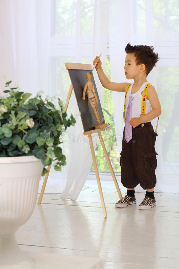 在一个画架的一个小男孩油漆在屋子里 图库摄影