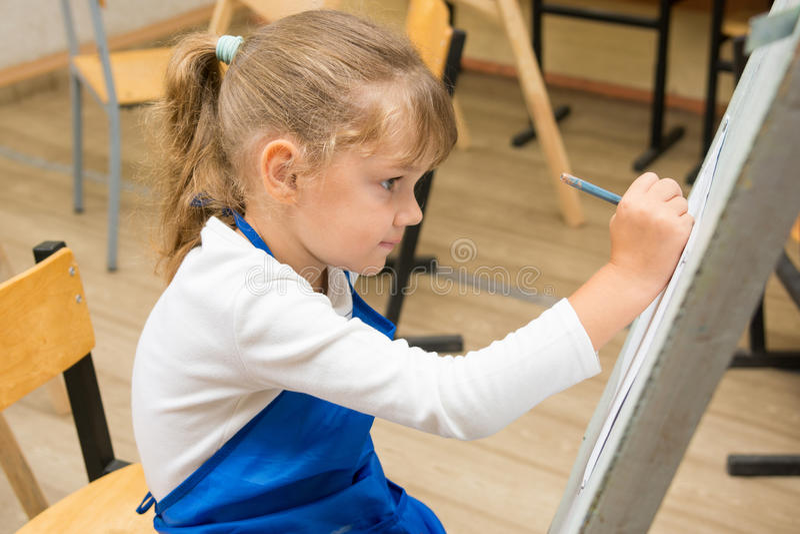 在一个画架的五年女孩油漆在图画教训 免版税库存图片