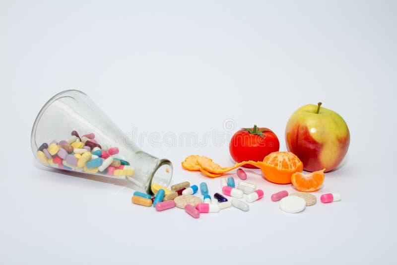 在一个玻璃容器的五颜六色的医疗药片在白色背景 图库摄影