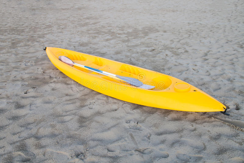 在一个轻的沙滩的黄色独木舟 库存照片
