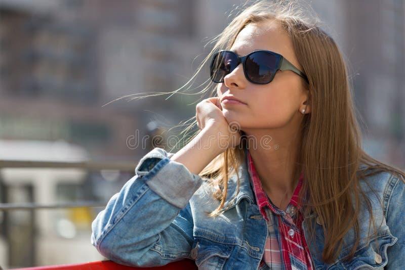 在一个年轻美丽的沉思女孩的档案的画象sunglas的 免版税库存图片
