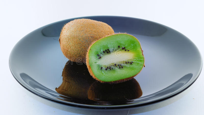 在一个黑色的盘子的猕猴桃 免版税库存照片