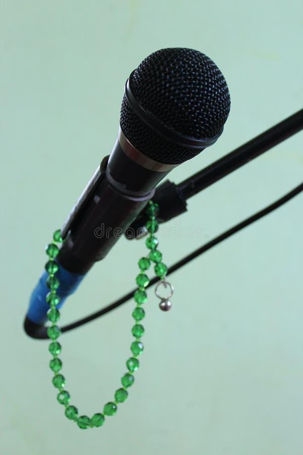 在一个绿色背景和念珠的话筒 免版税图库摄影