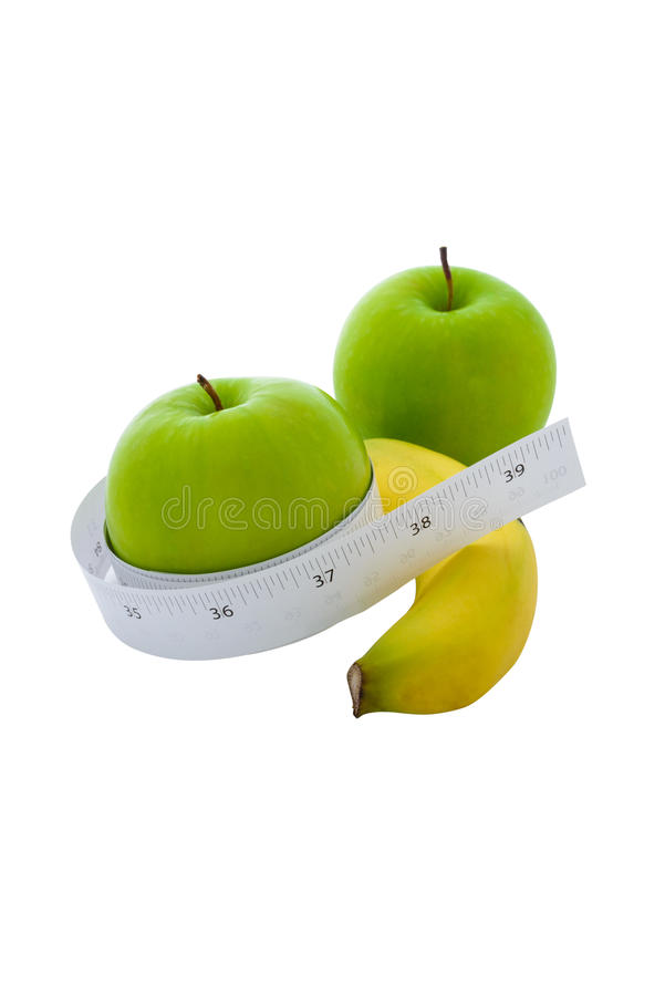 在一个绿色苹果和香蕉附近被包裹的测量的磁带 免版税库存照片