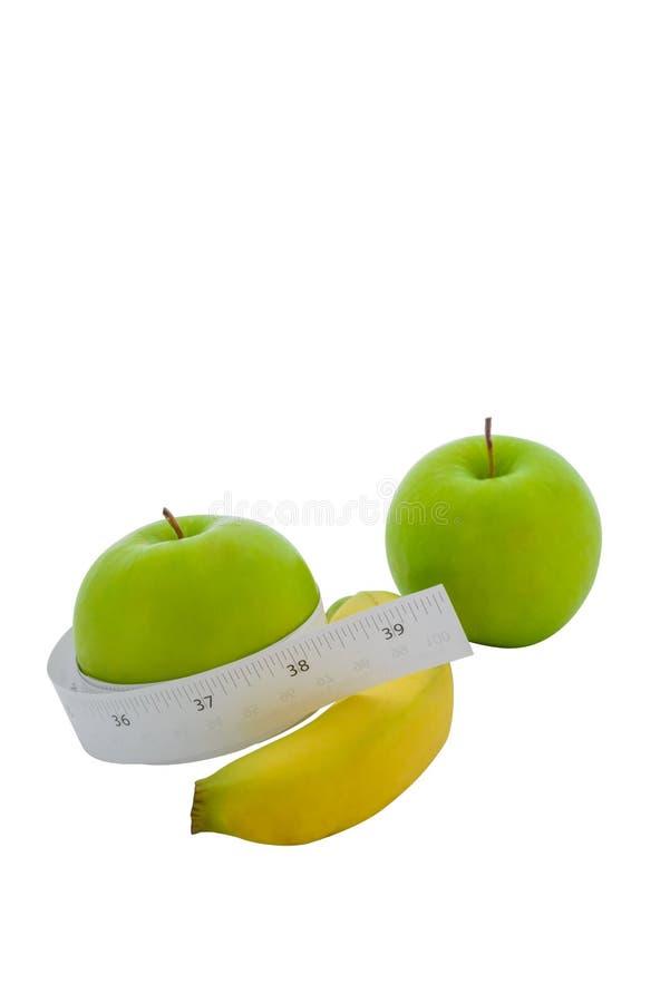 在一个绿色苹果和香蕉附近被包裹的测量的磁带 库存照片