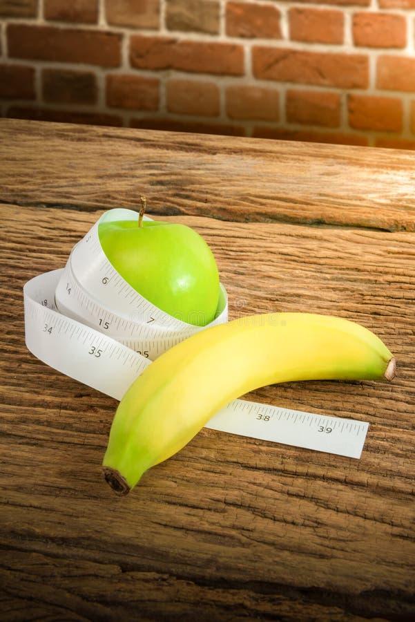 在一个绿色苹果和香蕉附近被包裹的测量的磁带 库存图片