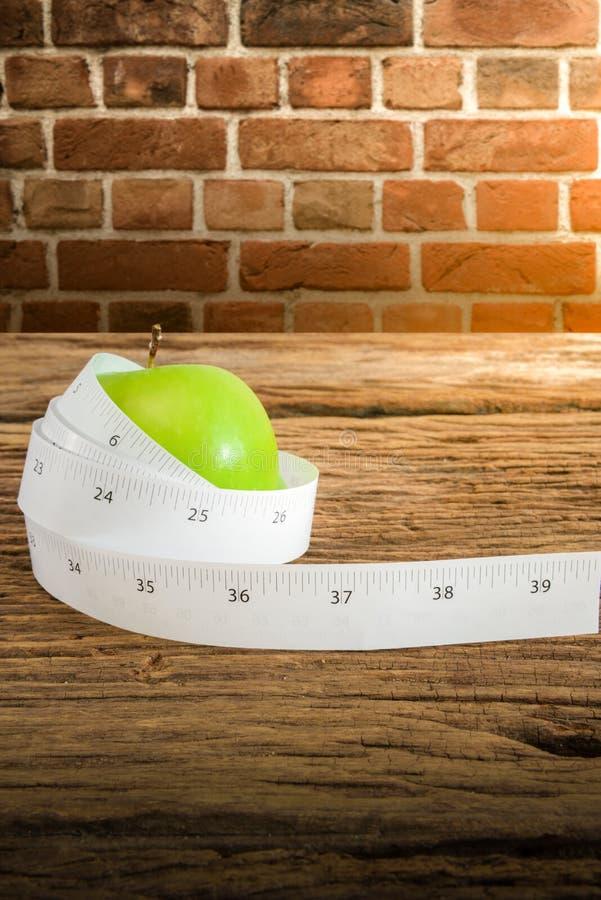 在一个绿色苹果附近被包裹的评定的磁带 免版税库存照片