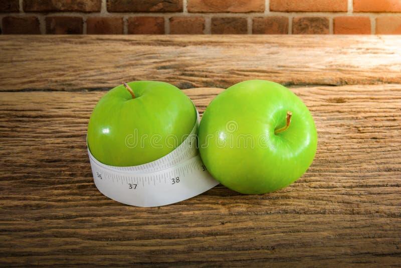 在一个绿色苹果附近被包裹的评定的磁带 库存图片