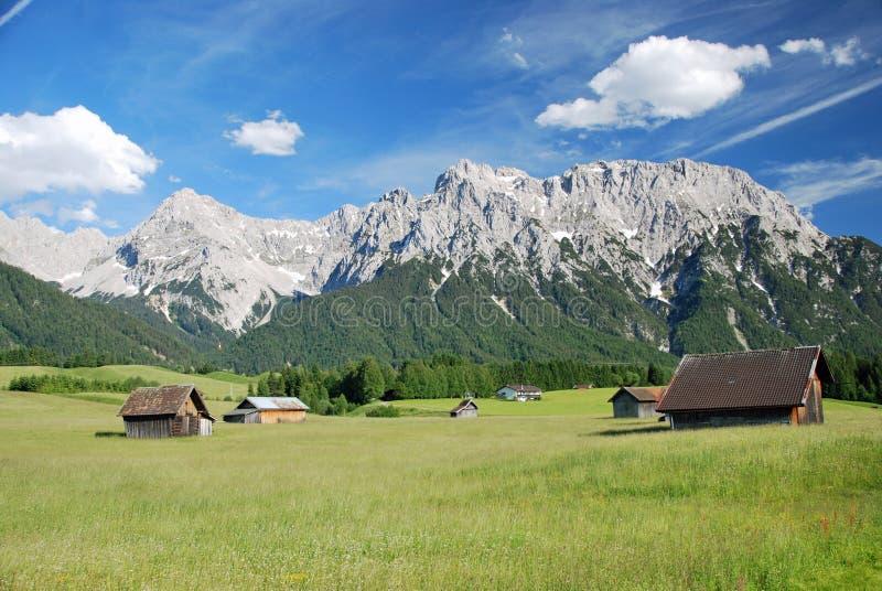 在一个绿色草甸的几个木小屋在山前面在巴法力亚阿尔卑斯 免版税库存照片
