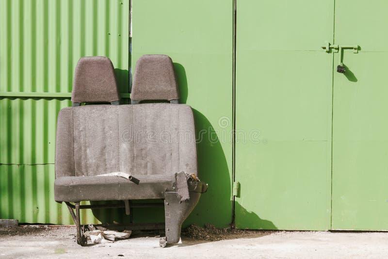 在一个绿色车库门前面的被放弃的汽车座位 免版税库存照片